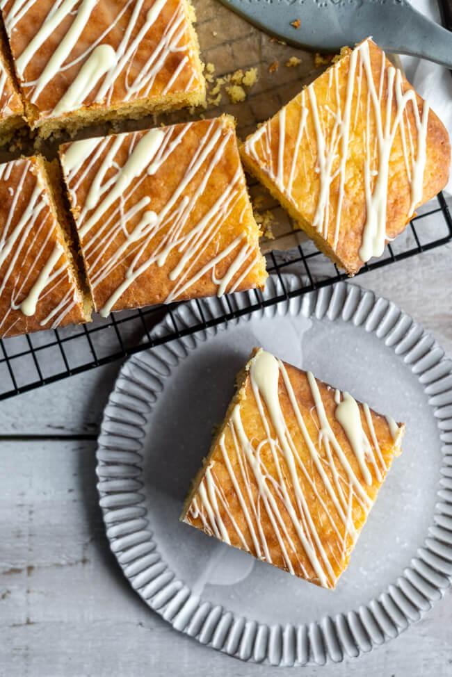 Einfacher Blechkuchen: Orangen-Kokos-Kuchen auf weißem Keramikteller und schwarzem Kuchengitter.