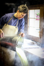 Schweizer Sennerin aus L'Etivaz beim Käsemachen.