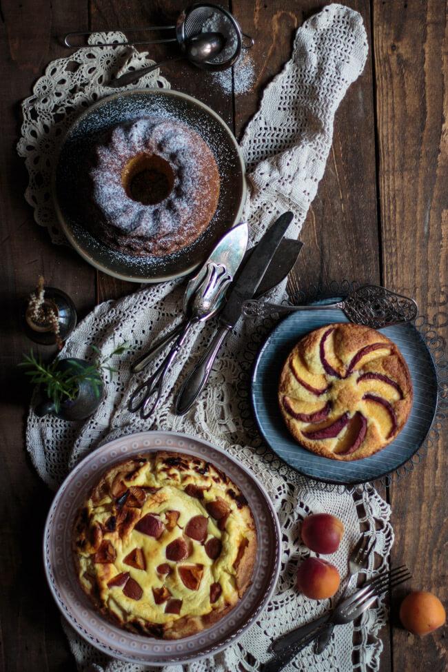 Drei Kuchen auf dunklem Holztisch mit Eierlikör, Aprikosen und Pfrisichen