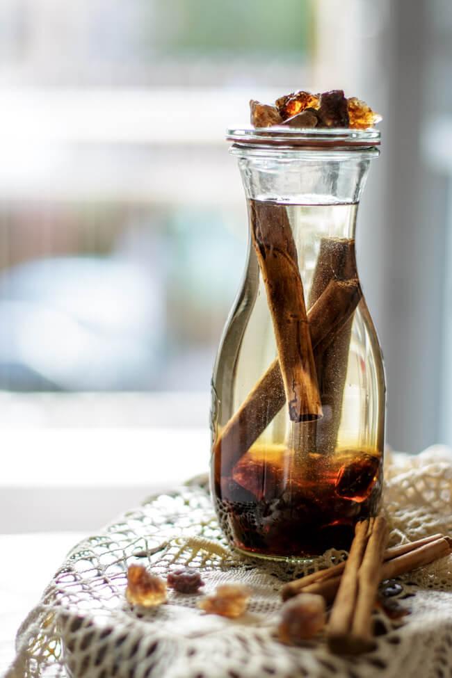 Zimt Likör in Weckflasche mit braunem Kandis auf Spitzendeckchen.