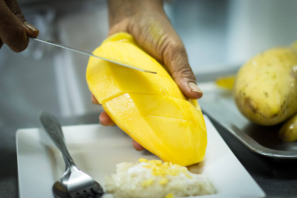 Thailänderin schneidet Thai Mango