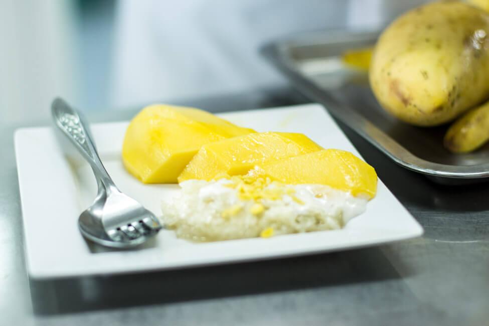 Mango mit Sticky Rice auf weißem Teller in Bangkok