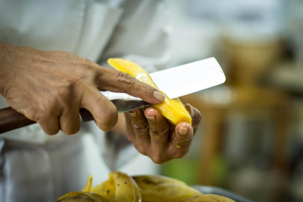 Thailänderin Chef Lenz schneidet gelbe Thai Mango