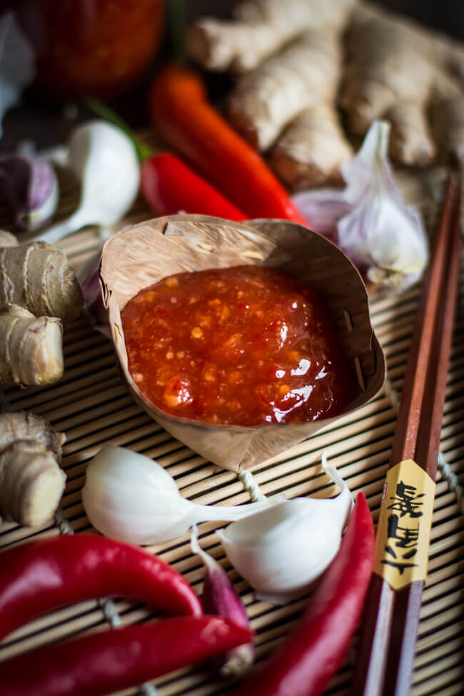thai sweet chili sauce in thailändischer dipschale mit knoblauch, chili und ingwer