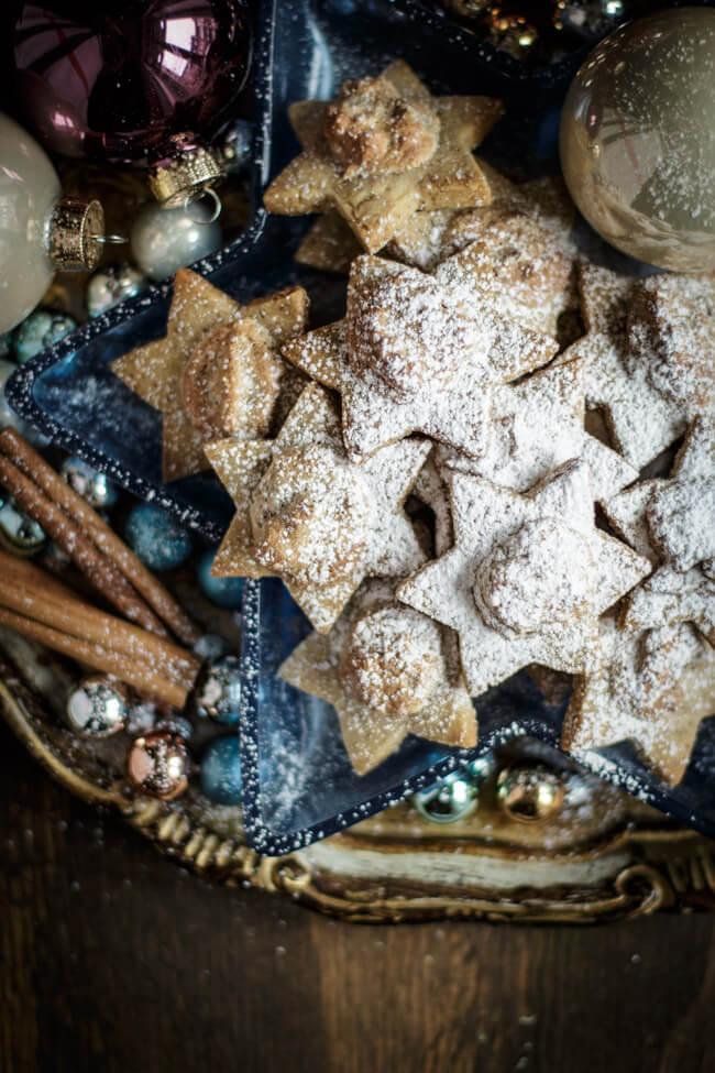 Merry Blogmas Dattelsterne auf weihnachtlichem Teller mit Puderzucker bestäubt