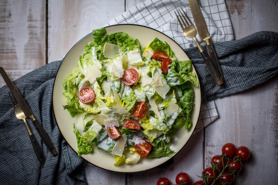 lowfat und lowcarb caesar salad auf weißem Porzellanteller und weißem Tisch