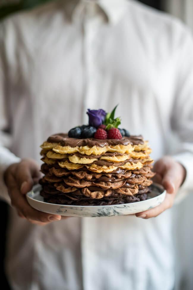 Mann in weißem Hend hält Ombre Torte mit Nougat Füllung