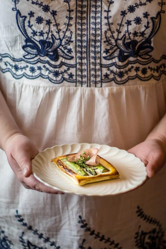 Frauen Hände halten Teller mit Spargel Blätterteig Tarteletts