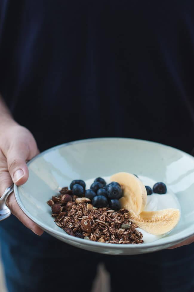 Granola mit Joghurt, Banane und Blaubeeren ind blauem Keramikteller