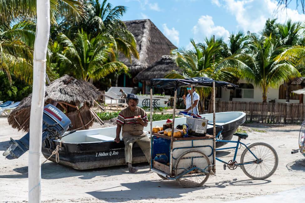Isla Holbox Mexiko weißer Sandstrand Traumstrand Meer Boote türkisblaues Meer Karibik Mann auf Boot Verkäufer