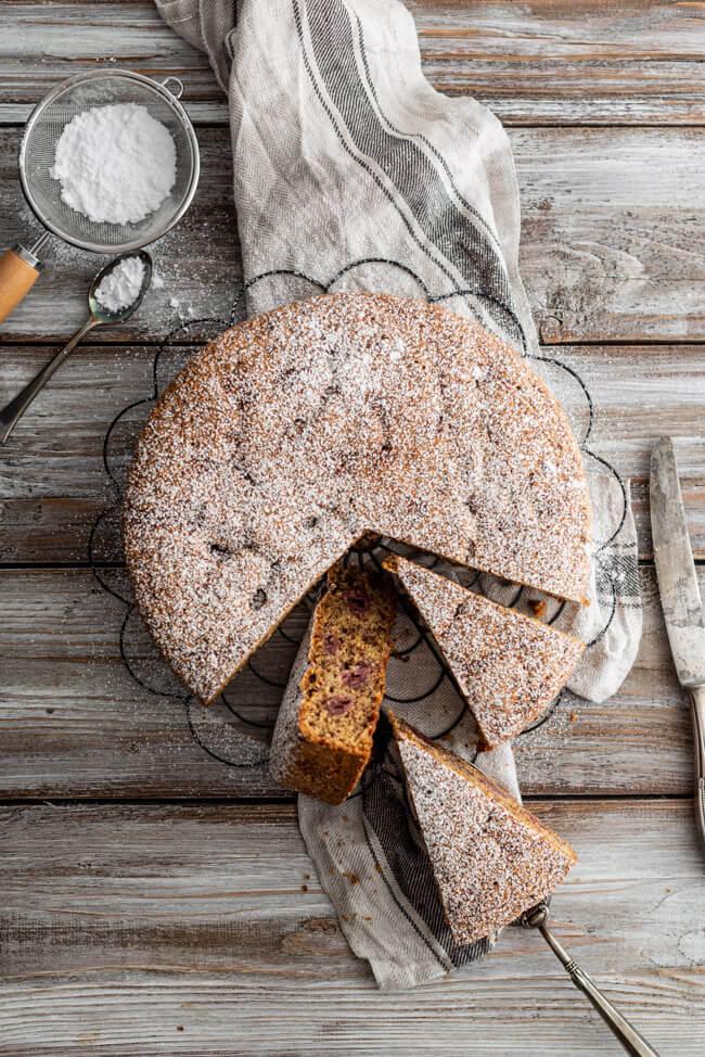 Schweizer Nusskuchen mit Kirschen Puderzucker Haselnüsse Schokolade Blockschokolade Sauerkirschen backen einfach saftig Kindergeburtstag ohne Alkohol