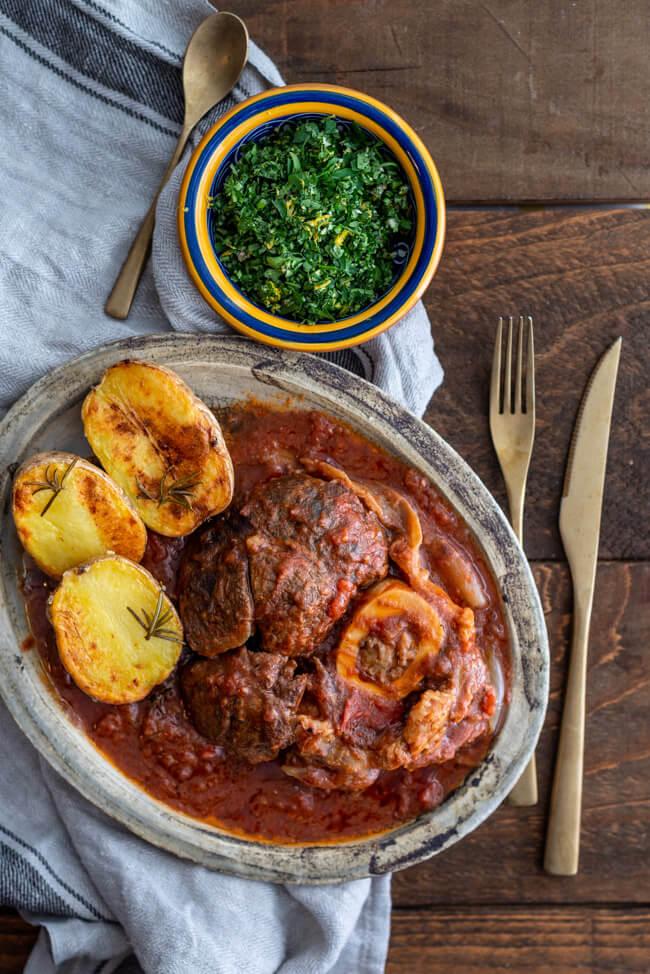 Ossobuco alla Milanese mit Gremolata Italien geschmorte Beinscheiben Rindfleisch Tomaten Schmorgericht Rosmarinkartoffeln Traditionell Familienessen Slowfood