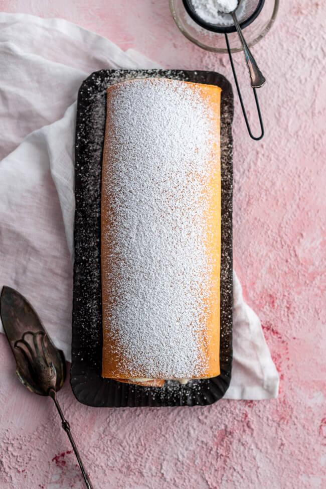 Rhabarber Bisquitrolle auf schwarzer Kuchenplatte.