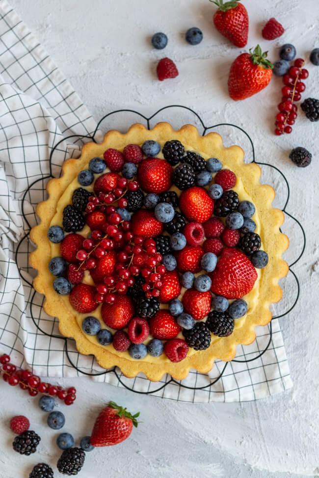 Obstkuchen mit Erdbeeren, Himbeeren, Heidelbeeren, Johsannisbeeren und Brombeeren und Eierlikörpudding auf schwarzem Tortengitter.