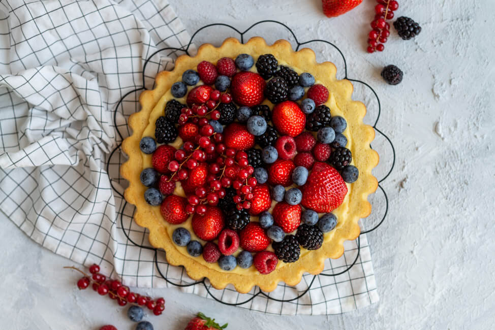 Obstkuchen mit Erdbeeren, Himbeeren, Heidelbeeren, Johsannisbeeren und Brombeeren und Eierlikörpudding auf schwarzem Tortengitter. #Bisquit #Obstkuchenboden #Eierlikörpudding
