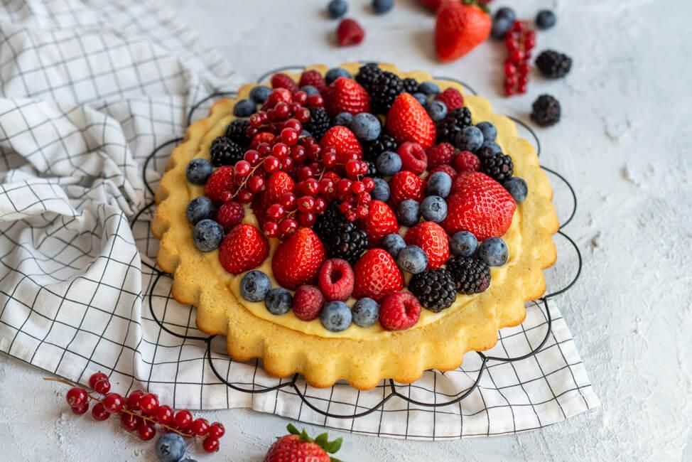 Obstkuchen mit Erdbeeren, Himbeeren, Heidelbeeren, Johsannisbeeren und Brombeeren und Eierlikörpudding auf schwarzem Tortengitter. #Erdbeerkuchen #Beerenkuchen #Sommer #Dessert