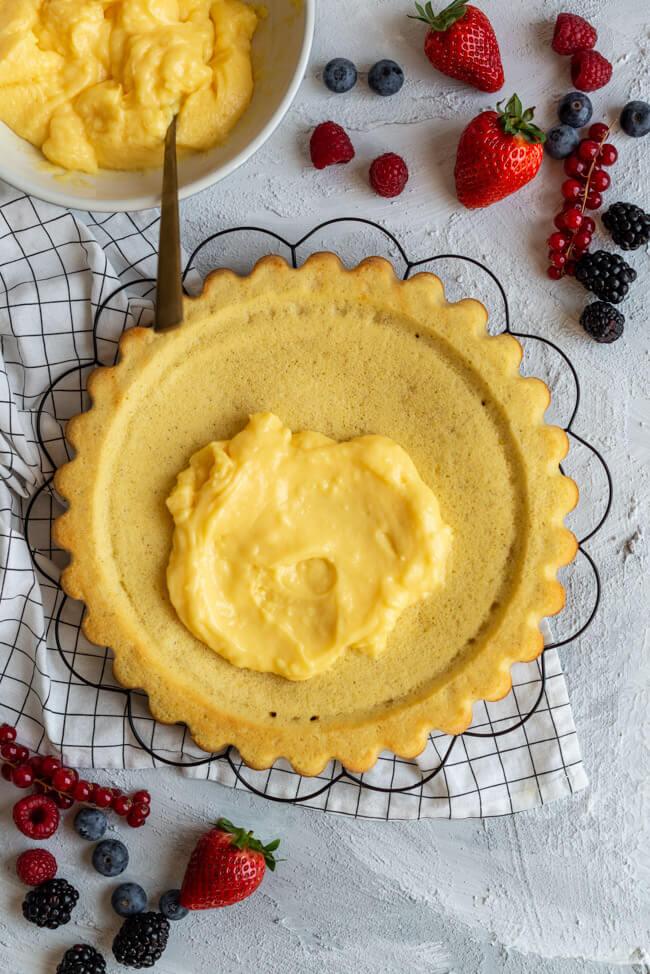 Obstkuchenboden wird mit Eierlikörpudding bestrichen. #Pudding #Eierlikör #Beeren #Kuchenboden #Bisquitboden