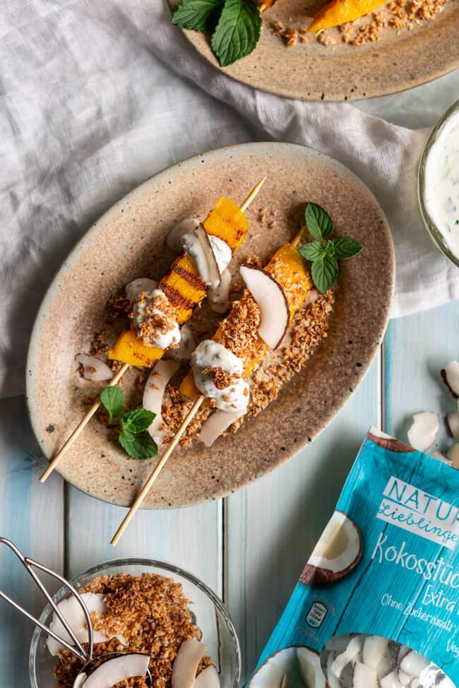 Gegrillte Mango Spieße mit Kokos-Knusper Topping und Limetten-Minte-Joghurt auf Keramiktellern und blauem Holzuntergrund.