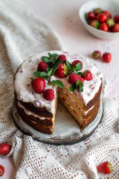 Naked Cake ala Himbeer-Limetten-Torte angeschnitten auf Keramik Tortenplatte und hellem Untergrund.