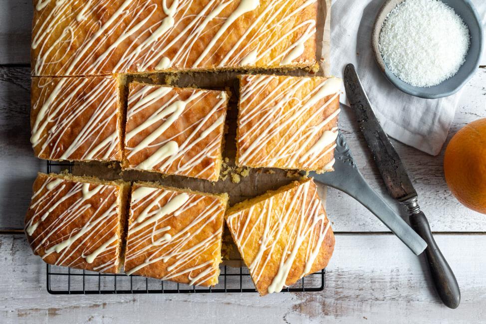 Einfacher Blechkuchen: Orangen-Kokos-Kuchen auf schwarzem Kuchengitter mit weißer Schokolade verziert.