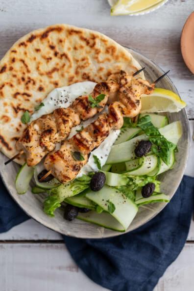 Griechische Hähnchen Souvlaki Spieße auf Pita Brot mit Tzatziki und Gurkensalat mit Oliven und Zitronen.
