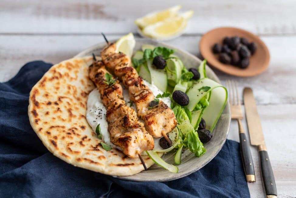 Griechische Hähnchen Souvlaki Spieße auf Pita Brot mit Tzatziki und Gurkensalat und Oliven auf Keramikteller.