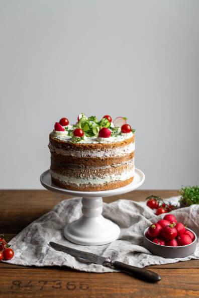 Brotzeittorte mit Pfälzer Leberwurst, Schnittlauchfrischkäsecreme und Radieschen-Frischkäsecreme. Dekoriert mit Meerrettichsahne, Cherrytomaten und Gurken auf weißer Tortenplatte.