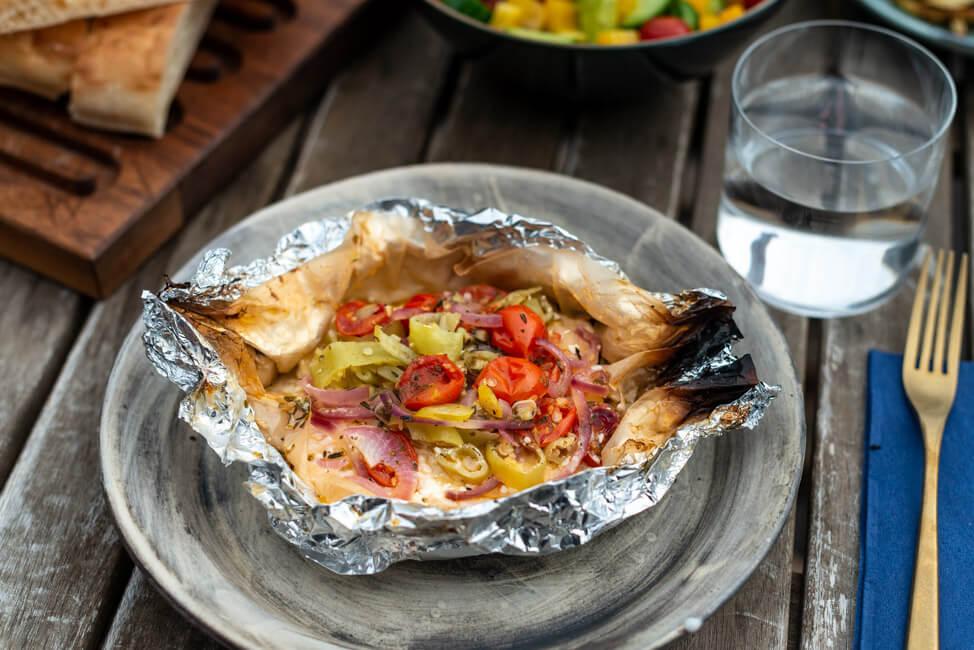 Feta Päckchen vom Grill mit Tomaten, Zwiebeln, Chili, Knoblauch und Zitrone in Backpapier und Alufolie.