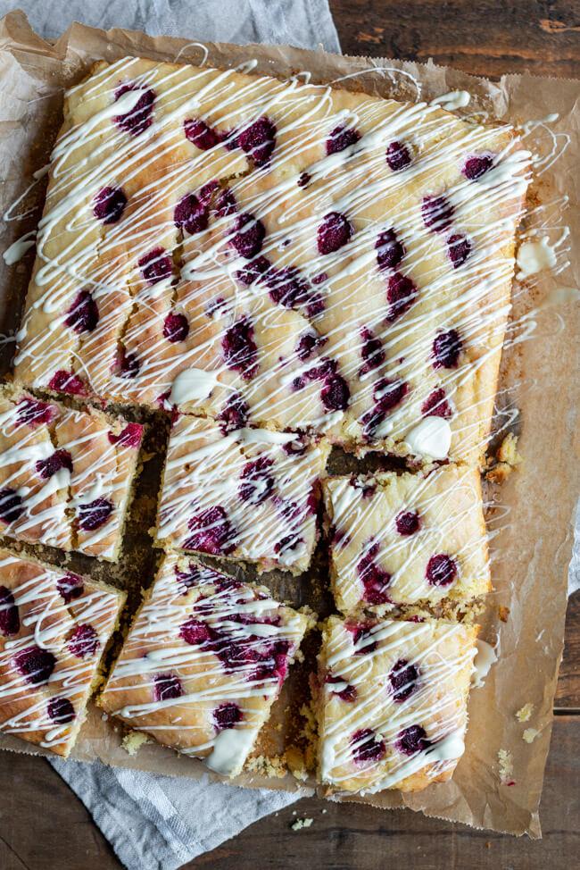 Kokos-Limetten-Kuchen mit Rum und Himbeeren auf Holzuntergrund. Ein einfacher und saftiger Blechkuchen für die ganze Familie.