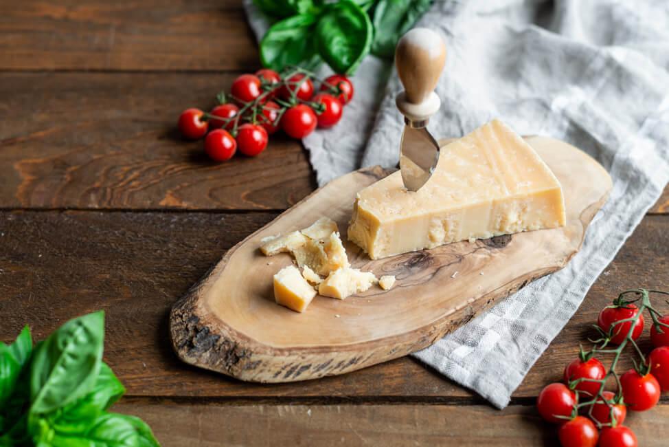 Parmigiano Reggiano auf Holzbrett mit Tomaten und Basilikum Dekoration.