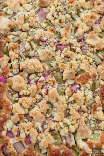 Rhabarber Haselnusskuchen mit knusprigen Streuseln auf einem großen Kuchenbrett.