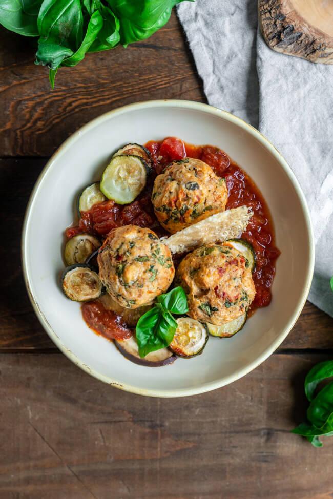 Mediterrane Semmelknödel auf Gemüse mit Parmigiano Reggiano auf einem hellen Teller.