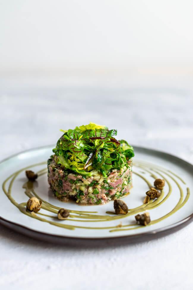 Vorspeise bei der Küchenschlacht im ZDF. Tina Kollmann bereitet Kalbstatar mit Wildkräutersalat, Kürbiskernöl-Mayonnaise und frittierten Kapern zu. Jurorin ist Sarah Henke.