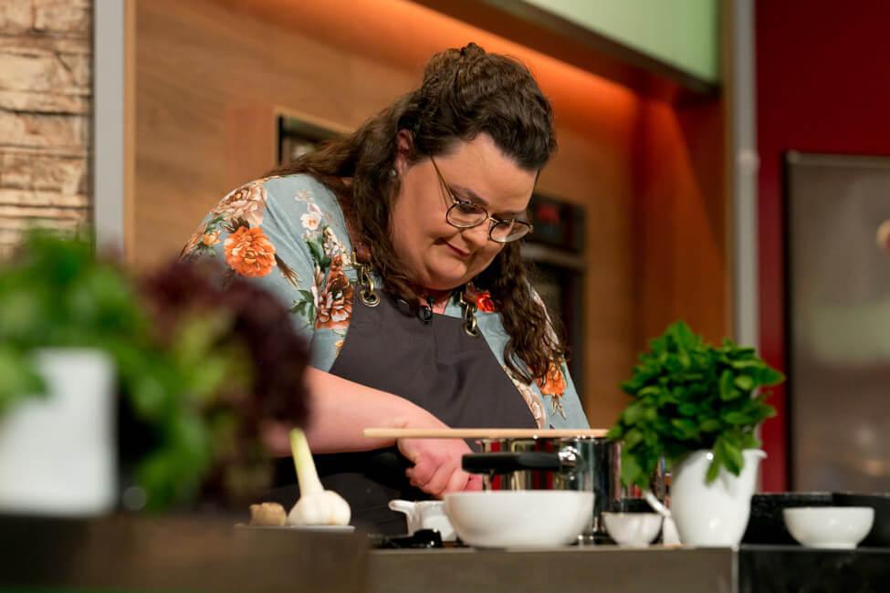 Portrait von Foodbloggerin Tina Kollmann im Studio von Die Küchenschlacht beim Kochen.