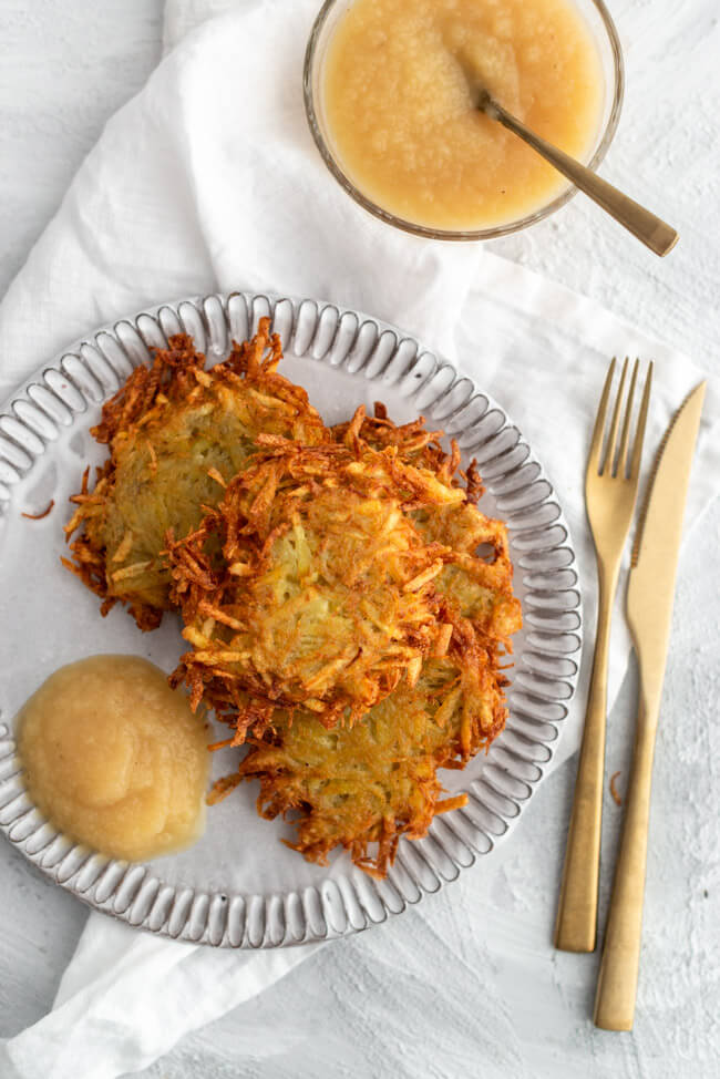 Fränkische Spezialität: Baggers mit Apfelmus auf weißem Keramikteller, auch bekannt als Kartoffelpuffer.