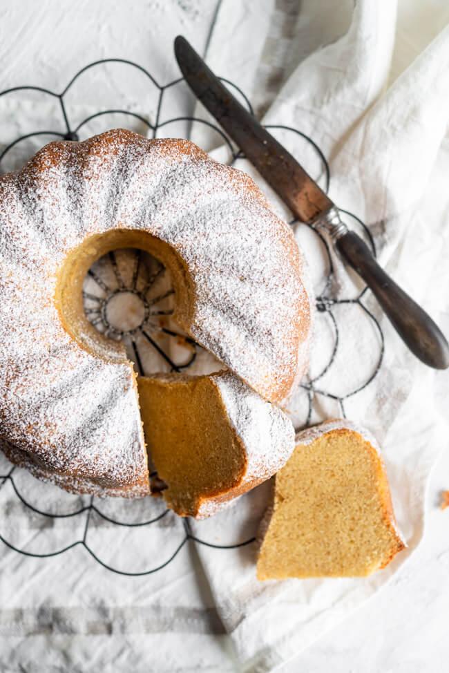 Fluffiger und saftiger Baileys Gugelhupf mit Puderzucker bestäubt auf schwarzem Kuchengitter.