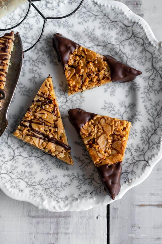Klassische Nussecken mit Haselnüssen und Mandeln und in Schokolade getauchten Ecken auf Kuchengitter und Porzellanteller.