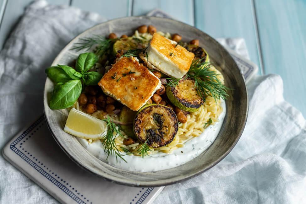 Griechische Orzo Pfanne mit gerösteten Kichererbsen, Zucchini, knusprigem Feta und Dill-Zitronen-Joghurt auf Keramikteller.