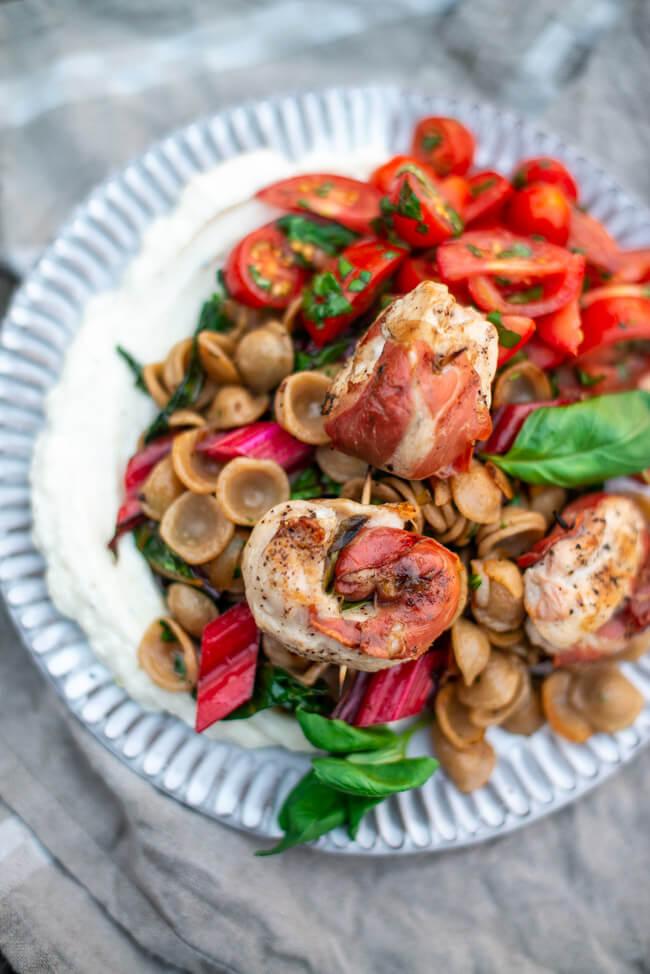 Saltimbocca-Röllchen aus Hähnchenbrustfilet mit Orecchiette und Mangold. Dazu cremiger Ricotta und Tomatensalat mit Basilikum.