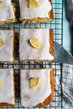 Zitronen-Mandel-Kuchen vom Blech auf schwarzem Kuchengitter. #backen #zitronenkuchen #mandeln