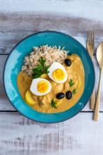 Aji de Gallina - Hähnchengeschnetzeltes aus Peru mit gekochtem Ei, schwarzen Oliven und Reis in blauem Keramikteller.