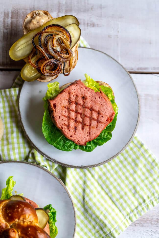 Gegrillter Leberkäse mit Gittermuster für Leberkäseburger im Laugenbrötchen.