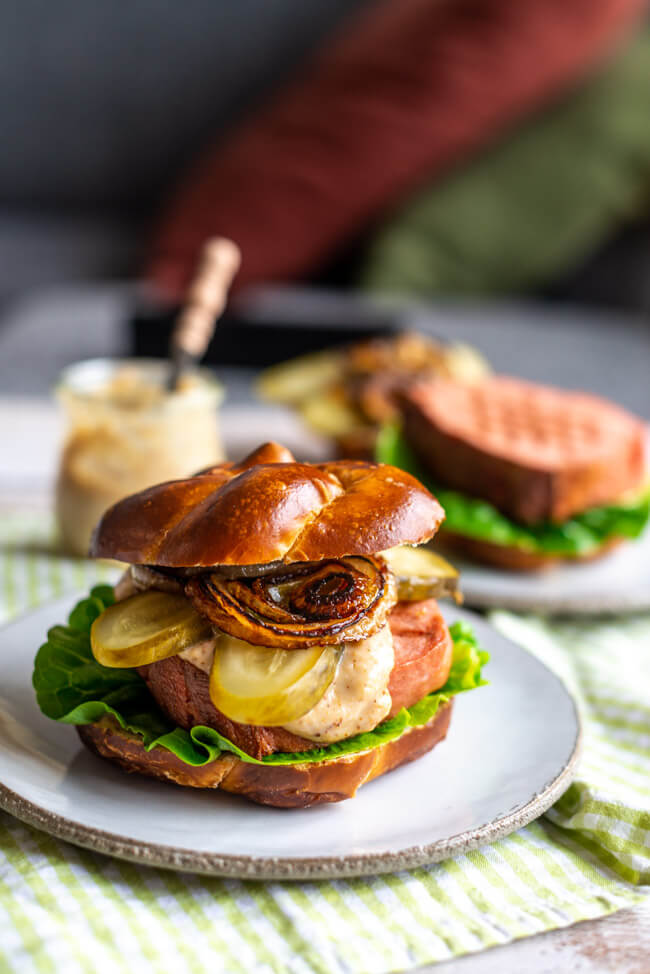 Leberkäse Burger im Laugenbrötchen mit Essiggurken, gebratenen Zwiebeln und Meerrettich-Senf-Mayo