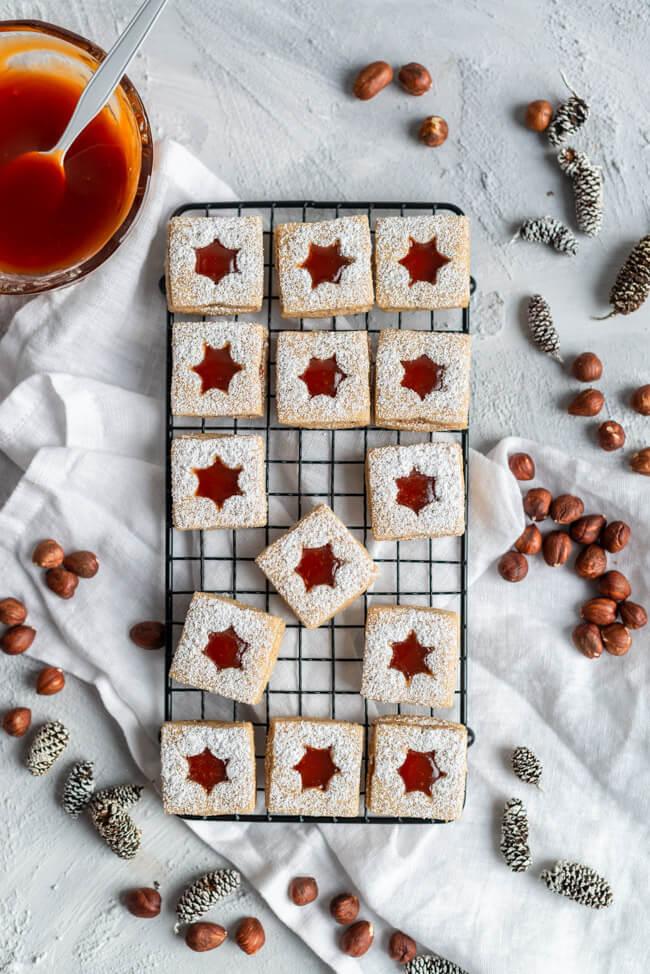 Köstliche Weihnachtsplätzchen: Haselnuss-Spitzbuben mit Hiffenmark auf schwarzem Metallgitter.