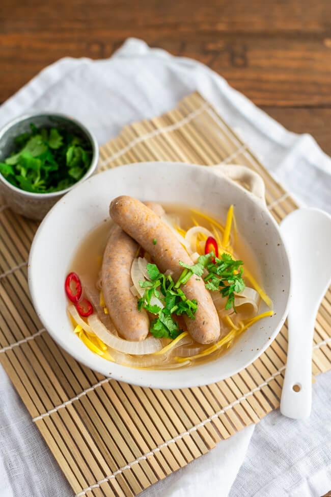 Saure Zipfel Thai Style mit reichlich Zwiebeln und Karotten im Essigsud mit Kaffirlimettenblättern und Zitronengras. Zu den Bratwürsten im Essigsud gibt es Koriander und rote Chili.