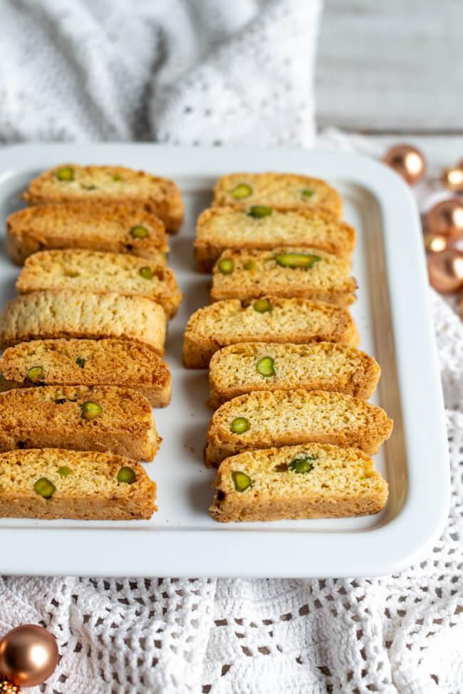 Leckere Weihnachts Cantuccini mit Orange, Kardamom, Pistazien, Vanille, Zimt und Kardamom auf einem weißen Porzellanteller.