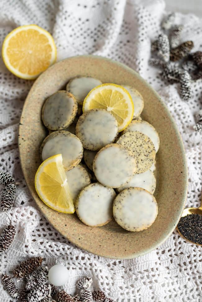 Zitrone-Mohn-Taler - köstliche Weihnachtsplätzchen mit Frischekick auf hellem Porzellanteller.
