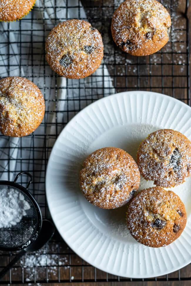 Einfache Chocolate Chip Muffins mit Puderzucker bestäubt auf schwarzem Kuchengitter.