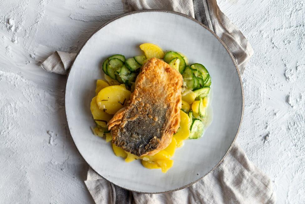 Gebackenes Fränkisches Karpfenfilet mit Kartoffel-Gurken-Salat und Essig-Öl-Vinaigrette.