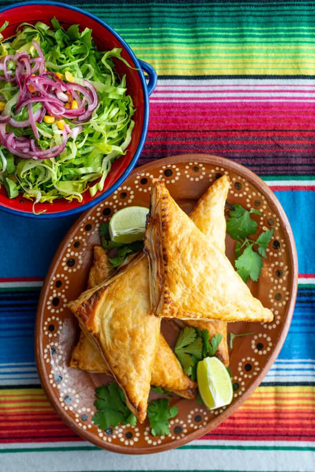 TexMex Blätterteigtaschen mit Tabasco und Limette auf rustikalem Tonteller. Dazu eine bunte Keramikschale mit Salat.